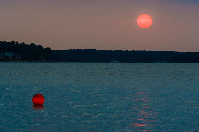 Red ball contrasting with twilight blue and pink glow at sunset on Lake Conroe, Texas.