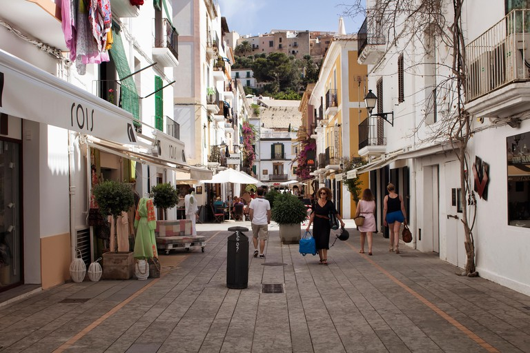 View of people walking on one of narrow, historical shopping streets in Ibiza old town. Image reflects culture and lifestyle of the island.