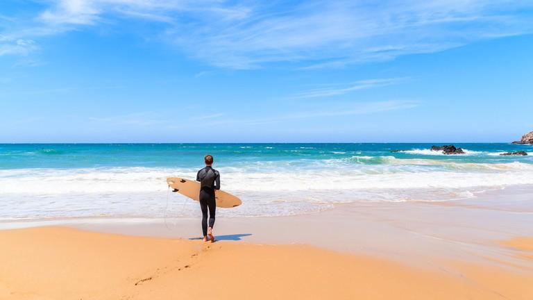 PRAIA DO AMADO BEACH, PORTUGAL - MAY 15, 2015: Surfer walking on Praia do Amado beach with ocean waves hitting shore. Algarve region is popular holida