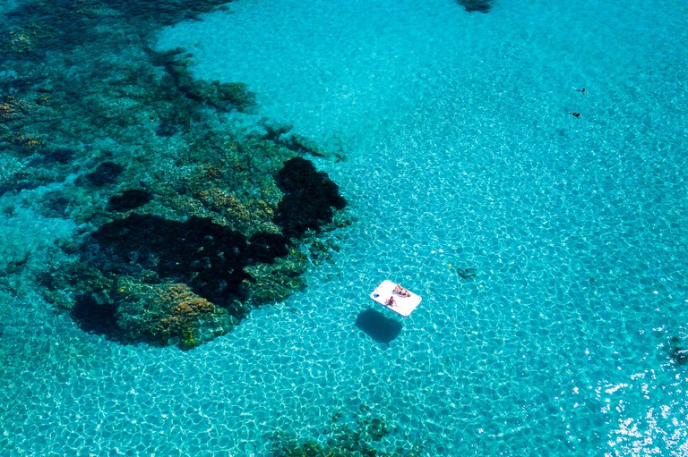 Aerial view of two people relaxing on a white beach mattress on an emerald and transparent Mediterranean sea. Emerald coast (Costa Smeralda), Sardinia