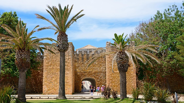 View of the entrance arch of the Governors Castle (Castelo dos Governadores) with palm trees in the foreground and tourists enjoying the setting, Lago
