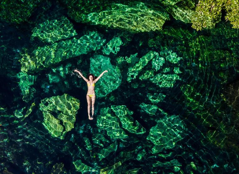 RREDRW Overhead woman floating in the Cristalino cenote,Quintana Roo, Mexico