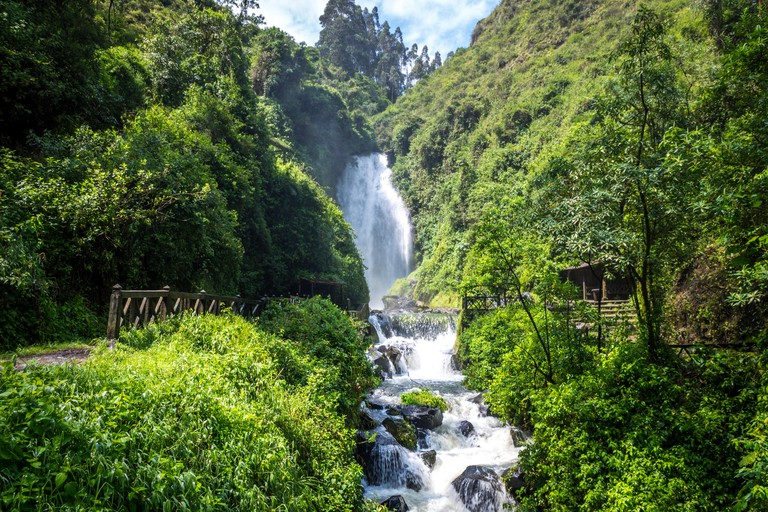 View of Peguche Waterfall in the mountains of Ecuador. It's surrounded by green forest full of vegetation