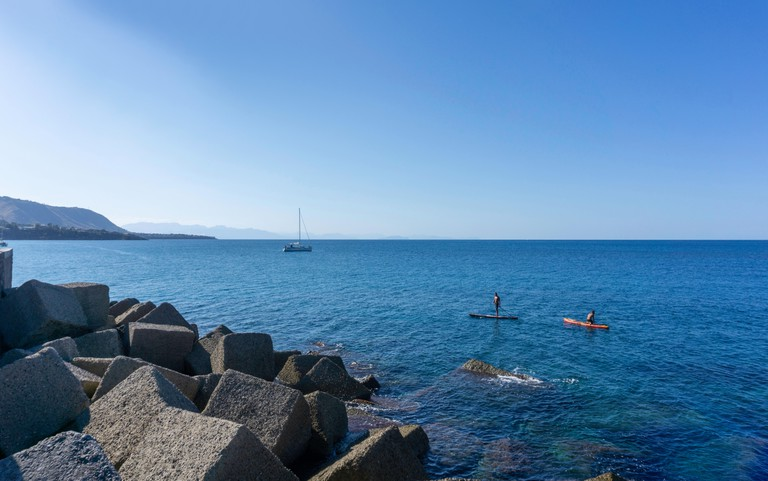 Off the coast of Cefalu, Sicily, Italy, two men paddle boarding in the clear blue waters of the mediterranean with a yacht in the distance.