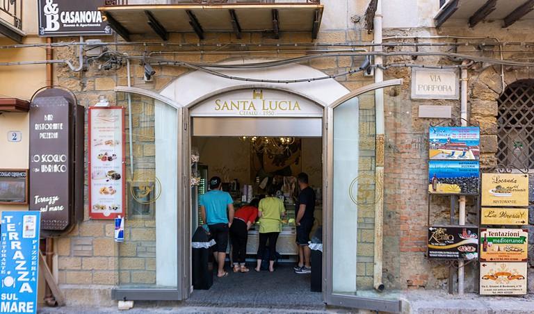 Customers choosing ice cream in the Santa Lucia Gelateria, ice cream store in Cefalu, Sicily, Italy.