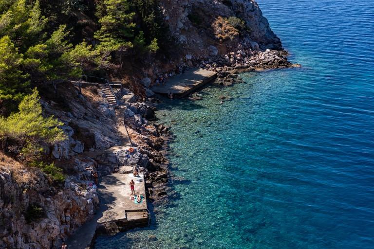 Cliffs and Avlaki beach in Hydra Island, Greece