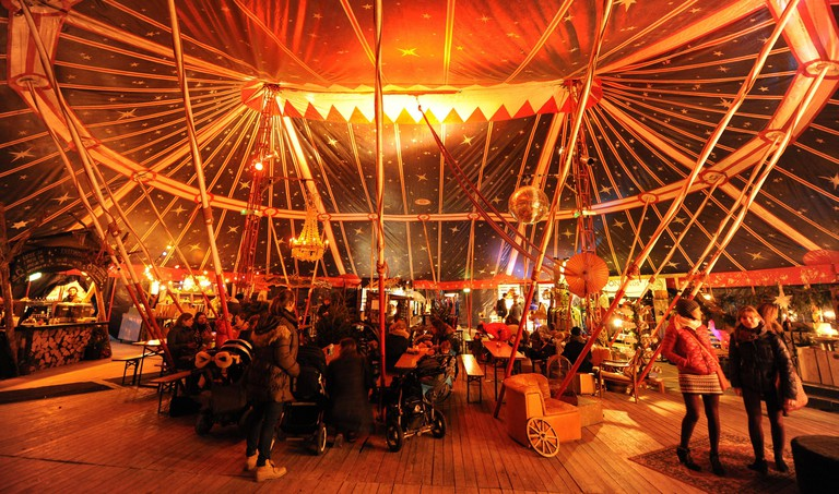 """Guests in a circus tent at the Christmas market """"Marchenbazar"""" in the cattle yard on the Munich slaughterhouse grounds. [automated translation]"""