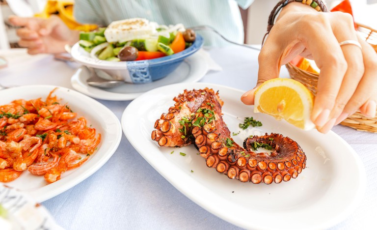 Close-up of a woman eating delicious seafood - shrimp and octopus grilled and vegetable salad. The concept of Mediterranean cuisine and healthy food