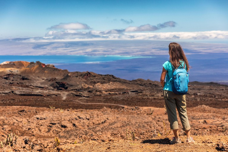 Galapagos tourist on adventure hiking looking at view on volcano Sierra Negra on Isabela Island. Woman on hike visiting famous landmark and tourist destination, Galapagos Islands Ecuador
