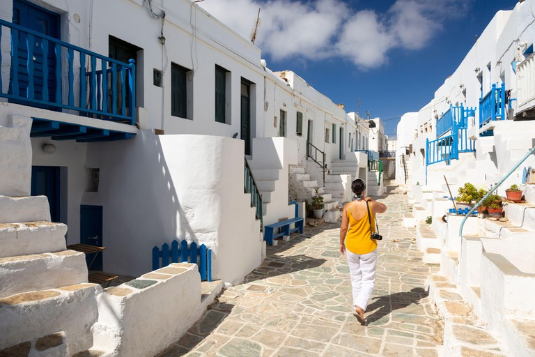 a woman walking down a street past traditional whitewash buildings in Folegandros, Cyclades Islands, Greece