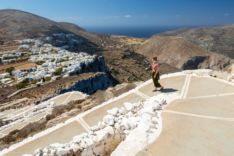 A young woman descending the footpath from the Church of Panagia, Folegandros, Cyclades Islands, Greece