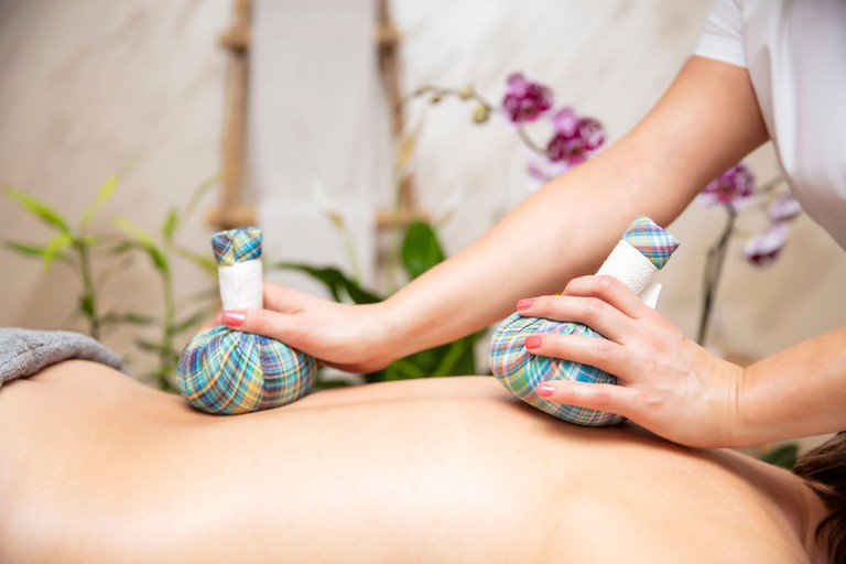 Calm young woman enjoying massage with herbal bags at the spa