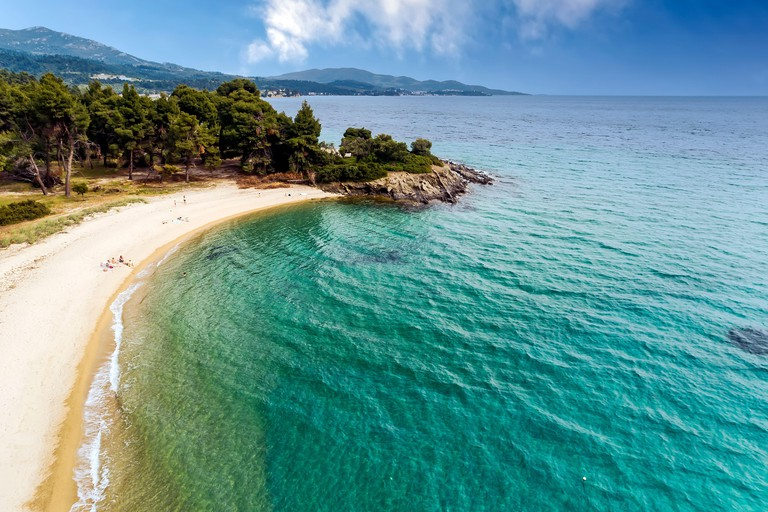 Aerial view of Lagomandra beach on the Sithonia peninsula, in the Chalkidiki , Greece. Beach and waves from top view. Turquoise water background from
