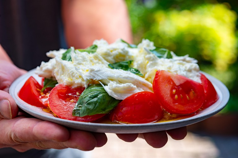 Waiter in cafe holding in hands fresh vegetarian caprese salad made from buffalo mozzarella cheese, fresh basil, tomatoes, olive oil. Italian food ser