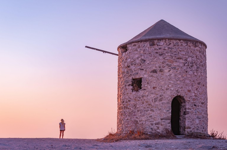 Lefkada, Greece. August 18th, 2011. A girl admires the view near one of the old mills of Milos Beach at sunset.