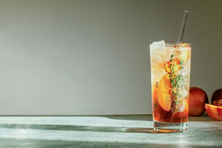 Refreshing peach iced tea Cuba Libre or Long Island iced tea cocktail in glass with straw. Summer refreshing fruit drink. Selective focus
