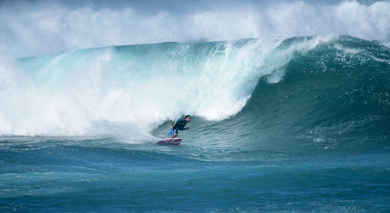 Surfer catches a massive wave in one of the first winter swells. Maui, Hawaii.