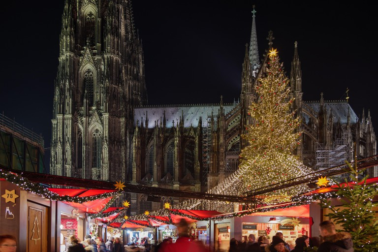 Night scenery, Weihnachtsmarkt, Christmas Market in Koln, with various decorated illuminate stalls in front of Christmas tree and Cologne Cathedral.