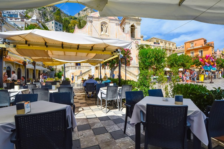 Cafe view on Piazza Aprile on the Mediterranean island of Sicily in Taormina, Italy on a warm summer day with a church and mountains behind