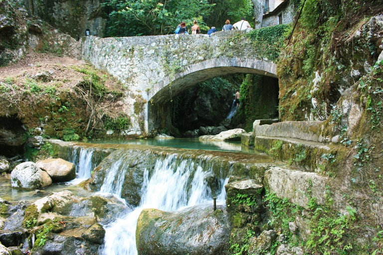 rocky bridge of candalla over the river waters in the Tuscan mountains in italy on summer
