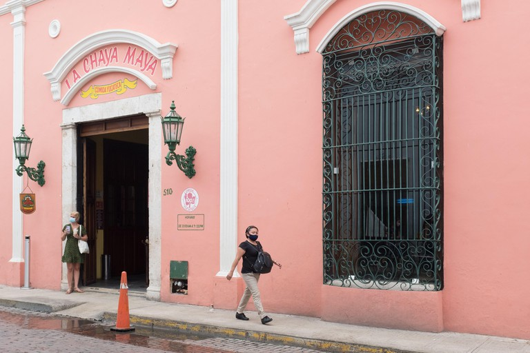 Lonely tourist in front of a restaurant: in a mostly empty downtown Merida during the Covid19 Pandemic, November 2020 - Many shops being closed and many businesses went out of business because of the Coronavirus restrictions. Merida, Yucatan, Mexico