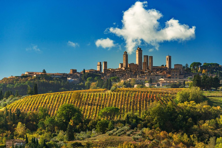 2D9BXFG the towers of San Gimignano stand tall above an autumn vineyard with a puffy cloud floating in the blue sky