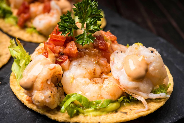 shrimp tacos on hard shell tortilla with Mexican garnish on dark wood background