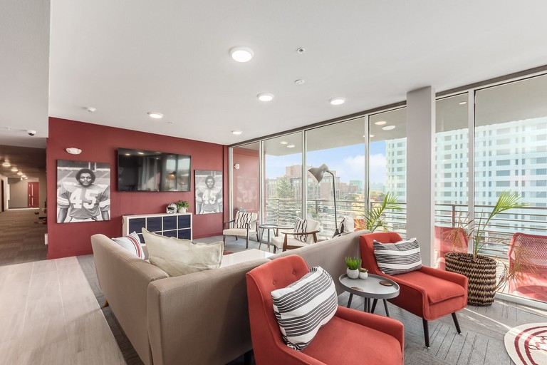 Inside The Urban with red and beige sofas and armchairs and a view over the city