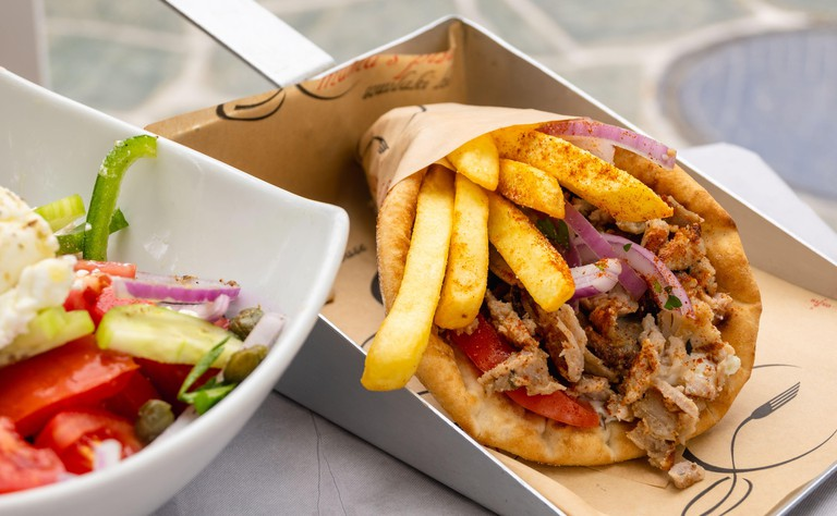 Folegandros, Greece - September 24, 2020: Traditional Greek souvlaki with chicken gyros, vegetables and fries served in pita bread.