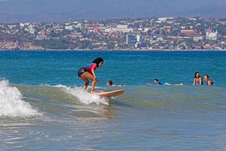 Young female surfers riding breaking wave on surfboards at Playa Zicatela near Puerto Escondido, San Pedro Mixtepec, Oaxaca, Mexico
