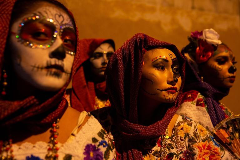 Mexican women dress as a Catrina during Paseo de las Animas (Walk of the souls).