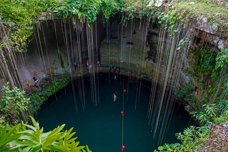 Tourists swimming in the Ik Kil Cenote, water-filled sinkhole outside Piste in the Tinum Municipality near Chichen Itza, Yucatan, Mexico