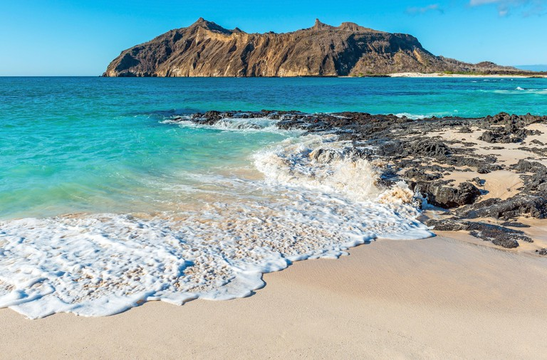 Galapagos beach landscape with strong waves, Stephens Bay with Witch Hill in background, San Cristobal island, Galapagos, Ecuador.