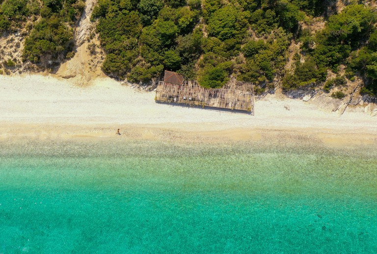 Aerial shot of a person walking on the empty Gidaki beach in Ithaca by the mountain and near an abandoned summer kiosk