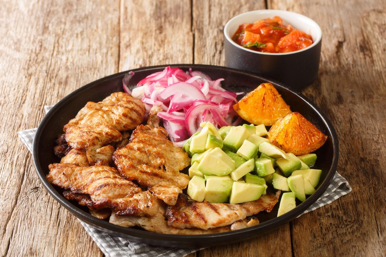 Poc Chuc this is a traditional Mexican Recipe from the Yucatan made of thin grilled pork cutlets with pickled onions and avocado closeup in the plate