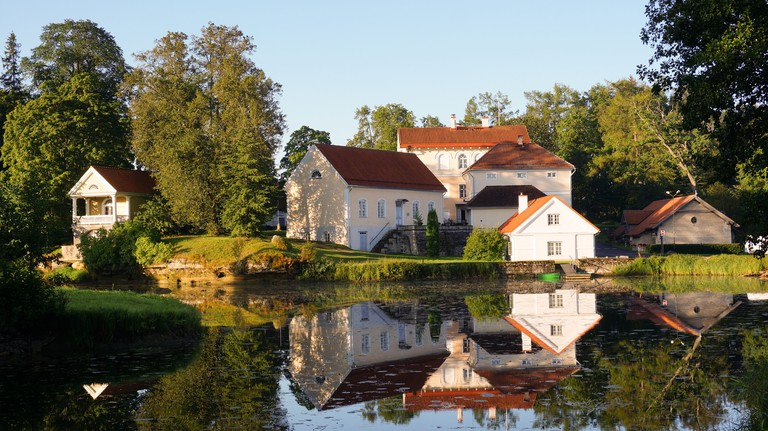 Guesthouses overlooking a lake in golden autumnal light at Vihula Manor Country Club & Spa