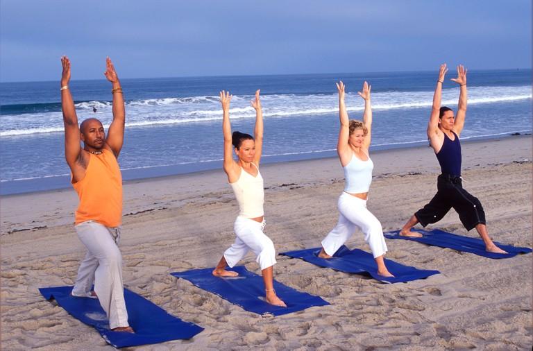 Multi ethnic friends doing yoga at sunrise on the beach Santa Monica CA
