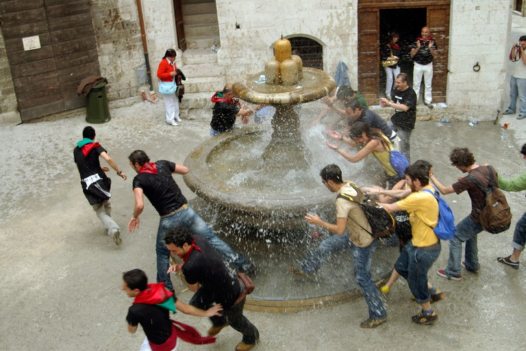 Tourists run around the fountain of madmen three times Gubbio Italy