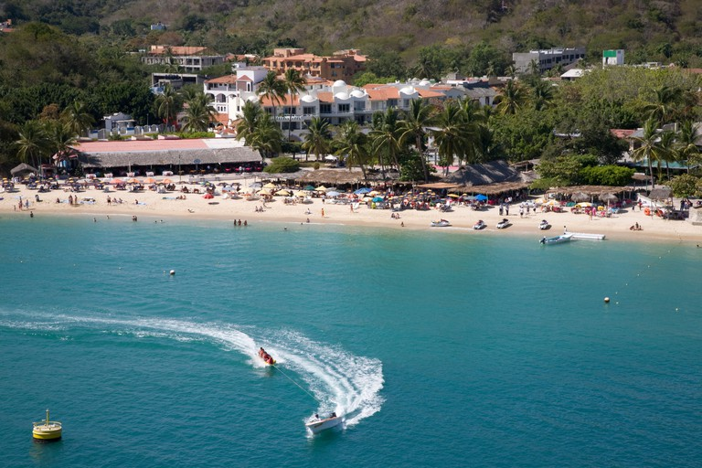 View of Huatulco beach resort with speed boat, Mexico.