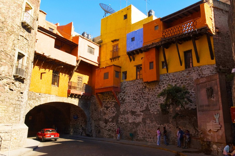 C3W1XG Mexico, Guanajuato, underground street with overhanging houses, red car through arched tunnel