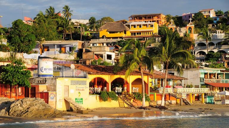 Mexico, Oaxaca, Puerto Escondido, Playa Principal. Colourful buildings amongst coconut palm trees lining the beach.