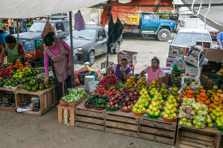 Four Mexican women selling produce outside at the Mercado Principal in Campeche, Mexico