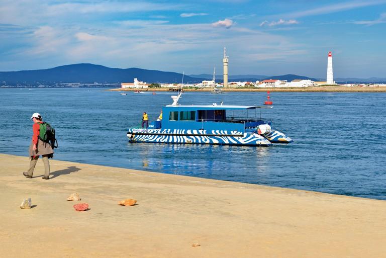 Portugal, Algarve: Katamaran ferry of Animaris arriving at Ilha Deserta in Nature Park Ria Formosa in Faro