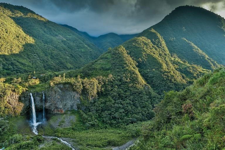 Ecuador, Tungurahua, Banos de Agua Santa, mountainous landscape with a waterfall in a tropical greenery caskets at sunset on a stormy sky
