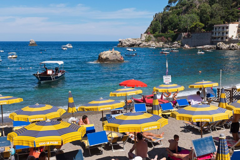 Holidaymakers on the beach at  Grotto Azzurra near Isolla bella, Sicily, Italy