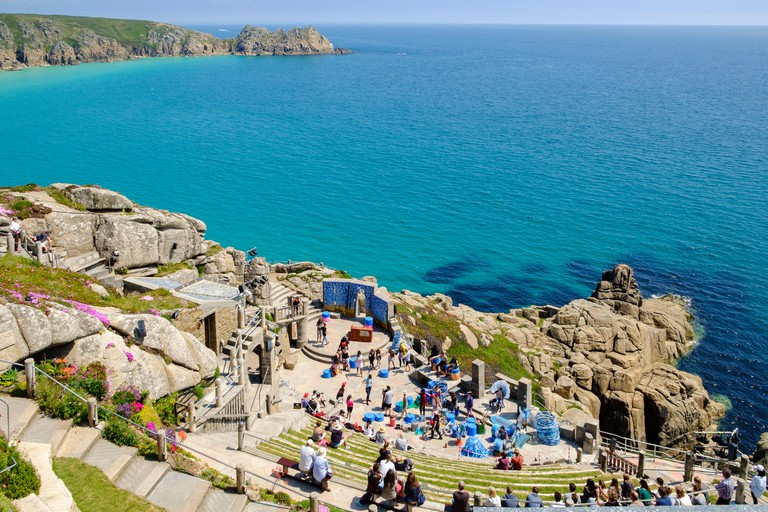 The Minack Theatre overlooking the sea at Porthcurno near Penzance, Cornwall, England, UK - with people watching a performance