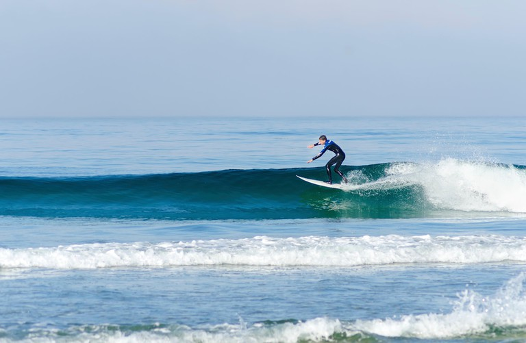 An American professional surfer man wearing a wet suit in the Pacific beach in San Diego, Southern California, in the United Sta