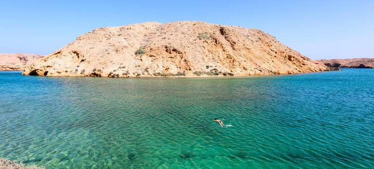 Woman snorkeling in a secret beach in Oman, between Muscat and Tiwi. Panoramic view of the sea and the mountain in the background