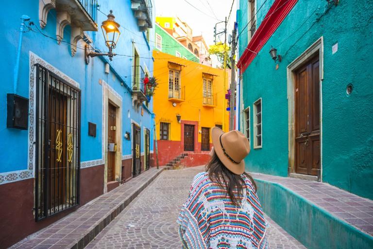 Tourist exploring colorful backstreets in Guanajuato, Mexico