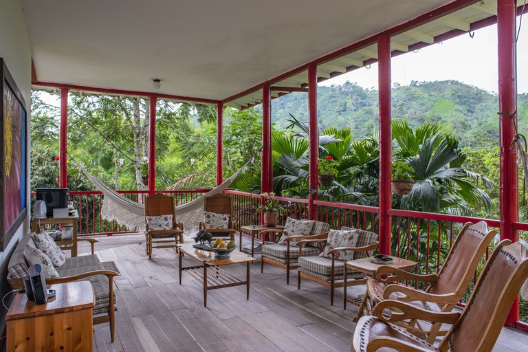 A hammock and chairs are surrounded by jungle vegetation on a deck at Hacienda Venecia, Manizales, in Colombia